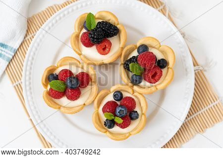 Delicious Pastry Mini Fruit Cream Cheese Pies Or Tart Cakes With Fresh Raspberry, Blueberry And Blac