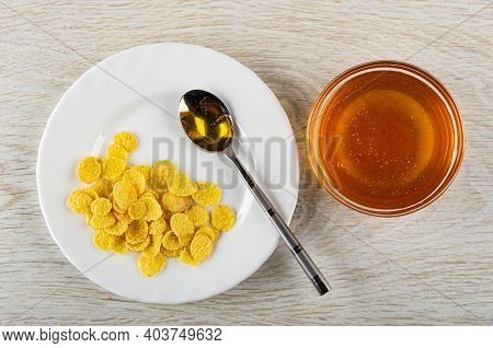 Teaspoon With Honey In White Plate With Corn Flakes, Transparent Bowl With Liquid Honey On Wooden Ta