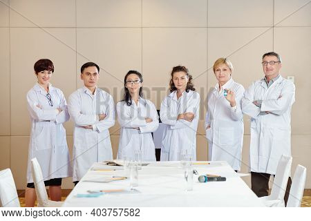 International Group Of Scientists In Labcoats Standing In Conference Room After Discussing Advantage