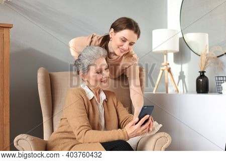 Happy Elderly Middle Mother Sitting On Chair With Her Daughter, Looking At Smartphone. Young Woman S