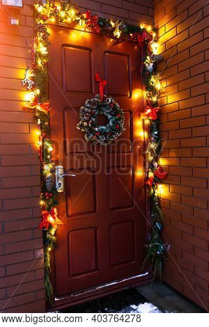 The Door Of The House Decorated With A Christmas Wreath.