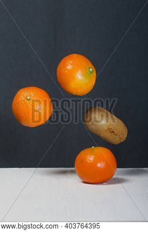 Tangerines And Kiwis Float Above The Table Surface. Fruit Levitation.