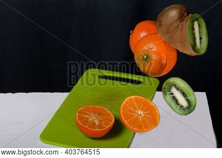 Tangerines And Kiwis Float Above The Table Surface. Some Are Cut Into Pieces. Fruit Levitation.