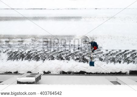 Worker Cleans Snow With A Shovel Top View.