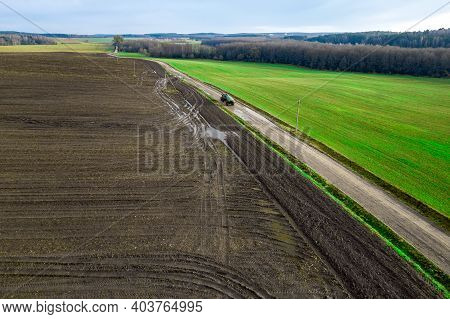 Panorama Of A Farmer's Field Top View. The Tractor Makes Organic Fertilizers.