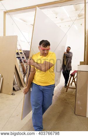Two Men Carry Furniture Materials In Their Workshop