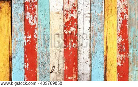 Texture of vintage wood boards with cracked paint of white, red, orange, yellow, cyan and blue color. Horizontal retro background with old wooden planks of different colors