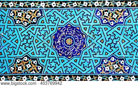 Detail of traditional persian mosaic wall with floral ornament,  Grand Jame Mosque (Masjid-e Jameh Mosque, Friday Mosque) in Yazd, Iran. The inscription in the center is a quote from the Quran