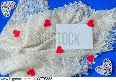 Love Scene With White Shawl, Rattan And Felt Red Hearts, Paper Card Note On Blue Background. Valenti