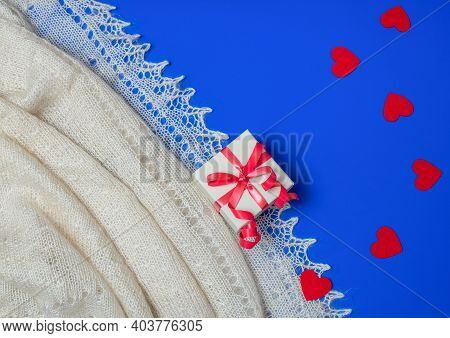 Holiday Scene With White Shawl, Gift Box And Felt Red Hearts On Blue Background. Love, Valentine Con