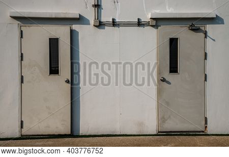 Two White Doors Of Machine Control Room. Passenger Elevator On The Rooftop Of The Condominium Buildi