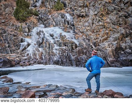 senior male hiker in a canyon of mountain river in winter scenery - Poudre River at Little Narrow above Fort Collins, Colorado