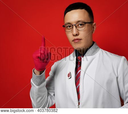 Portrait Of Young Man Doctor Urologist Or Proctologist Expert In Uniform Gown And Latex Gloves Holds