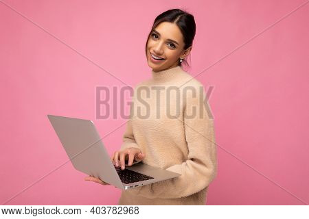 Photo Of Beautiful Smiling Happy Young Brunette Woman Wearing Beige Sweater Holding Netbook Computer