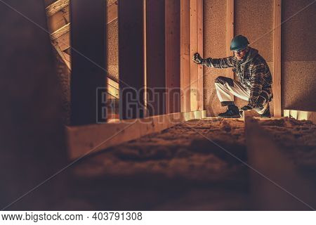 Caucasian Construction Worker In His 40s And His Wooden Attic Job. Professional Industrial Theme.