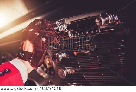 Oldtimer Driver Changing Radio Station Inside His Vintage Classic Car Close Up. Automotive Theme.