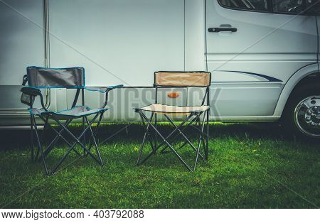 Campsite And Summer Recreation Theme. Two Empty Camping Deckchairs In Front Of Rv Camper Van Recreat