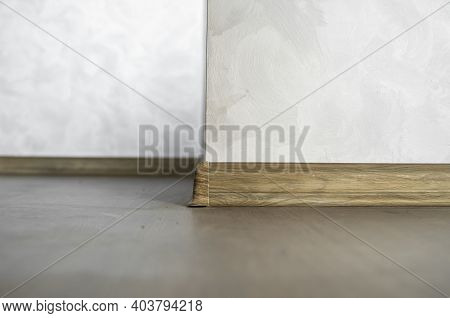 Laminate With Plastic Baseboard With A Wooden Texture. Newly Installed Wooden Laminate Flooring And
