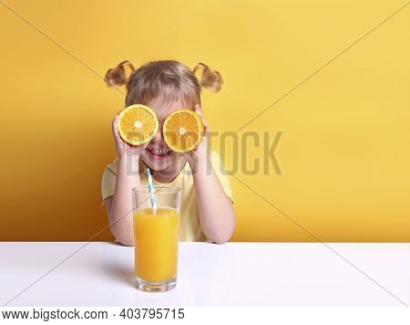 Child Girl With Oranges On Eyes Sitting At Empty Space Table With Glass Of Orange Juice.healthy Vita