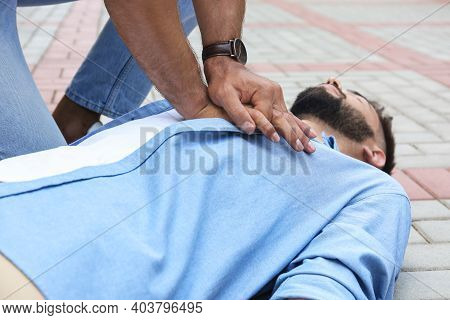 Passerby Performing Cpr On Unconscious Young Man Outdoors, Closeup. First Aid