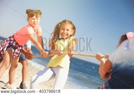 Cute Children Pulling Rope During Tug Of War Game On Beach. Summer Camp