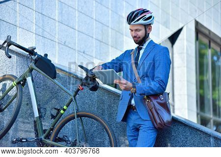 Businessman With Bike Using Digital Tablet In Park. Business And Urban Style Concept.