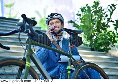 Businessman In Helmet Sitting On Stairs And Talking On Phone With Bicycle. Business And Urban Style