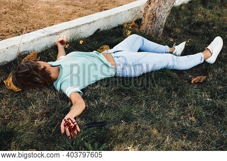 Crime Scene With Dead Woman's Body And Bloody Knife On Green Grass Outdoors. Detective Case