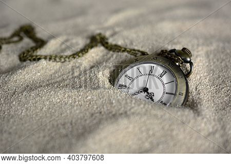 Old Pocket Watch Half Buried In Sand. Old Pocket Watch Lost In Sand