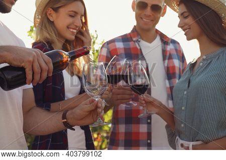 Friends Tasting Red Wine At Vineyard, Focus On Hands