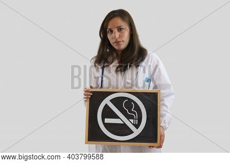 Serious Female Doctor Holding Blackboard With Ban On Smoking. Stop Smoking Concept. Isolated On Grey