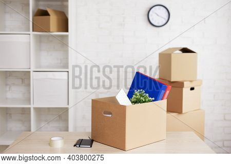 Financial Crisis, Bankruptcy And Moving Day Concept - Moving Boxes With Things On Table In Empty Mod