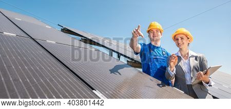 Manager and worker in photovoltaic power plant discussing maintenance of the solar farm