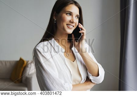 Portrait Of Business Woman, Holds Smartphone In Her Hands. Beautiful Girl Uses Mobile Phone For Work