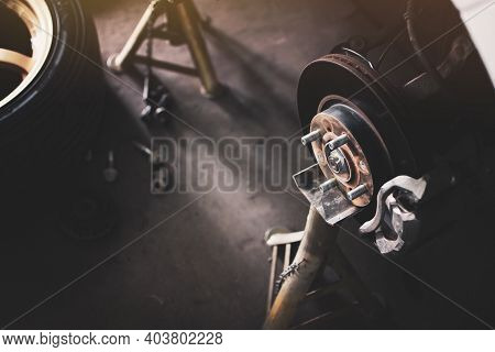 Brake Disc System Without Wheel On A Jack Stand Waiting Repair In Car Vehicle Repair Shop