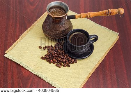 Black Turkish Coffee In Black Ceramic Cup And In A Vintage Copper Coffee Pot, Scattered Roasted Coff