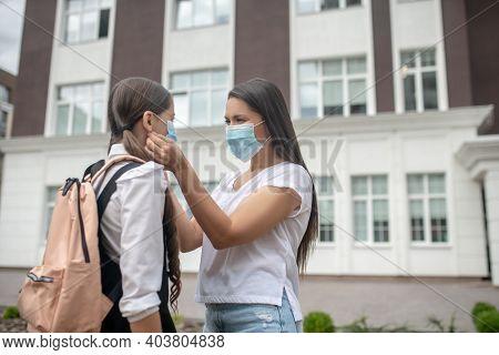 Woman And Schoolgirl Wearing Protective Masks In Schoolyard