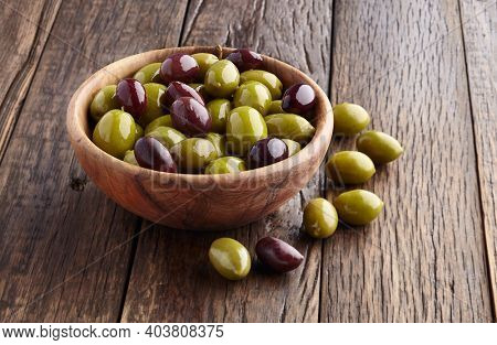 Green olives and kalamata olives on wooden background