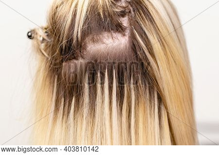 Hair Extensions Correction Procedure. Hairdresser Does Hair Extensions To Blonde Hair Lady In A Beau