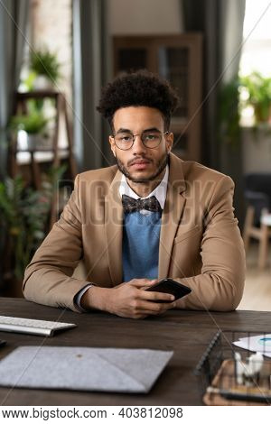 Portrait of man in eyeglasses sitting at his workplace with mobile phone and looking at camera at office