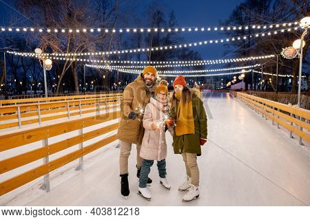 Portrait of happy family of three with sparklers standing on ice rink outdoors during Christmas holidays