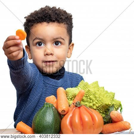 Close Up Portrait Of Cute Afro American Boy Showing Piece Of Carrot At Table. Kid Isolated On White