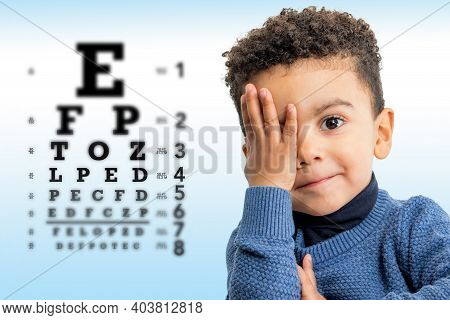 Close Up Face Shot Of Little Afro American Boy Testing Vision. Kid With Closing On Eye With Hand. Vi