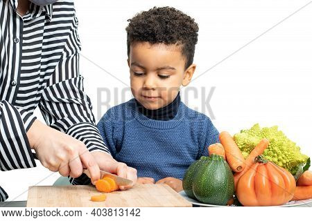 Close Up Portrait Of Little Afro American Boy Helping Chef Preparing Vegetable Dish. Hands Cutting C
