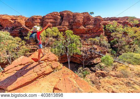 Panoramic View Of Woman At Kings Canyon Rim Walk With Footbridge Over Garden Of Eden, Watarrka Natio