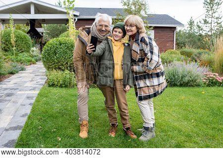 Happy youngster in casualwear and his affectionate grandparents looking in smartphone camera with smiles while making selfie