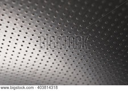 Dark Metal Wallpaper Or Background. Perforated Aluminum Surface With Many Holes, Hanging From Above