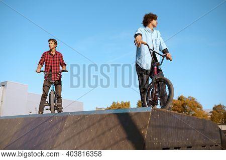 Bmx biker standing on ramp, training in skatepark