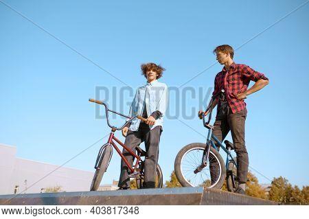 Bmx bikers, teenagers poses on ramp in skatepark