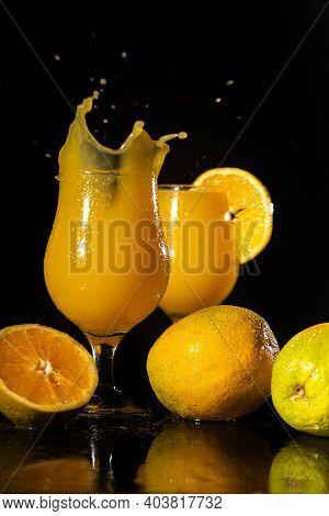 Orange Juice, Splash In Beautiful Glasses Of Orange Juice And Oranges Around, Black Background, Sele